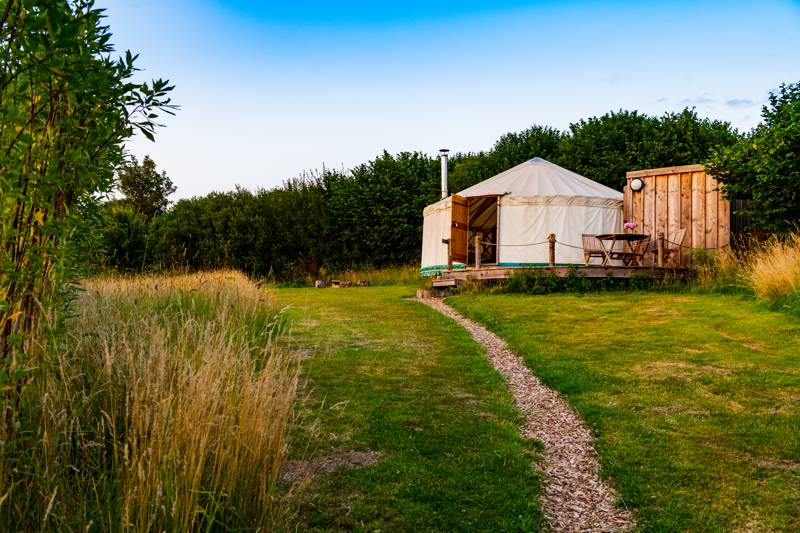 A wood-chip pathway leads to your luxury en suite yurt at Walnut Farm Glamping in Dorset.