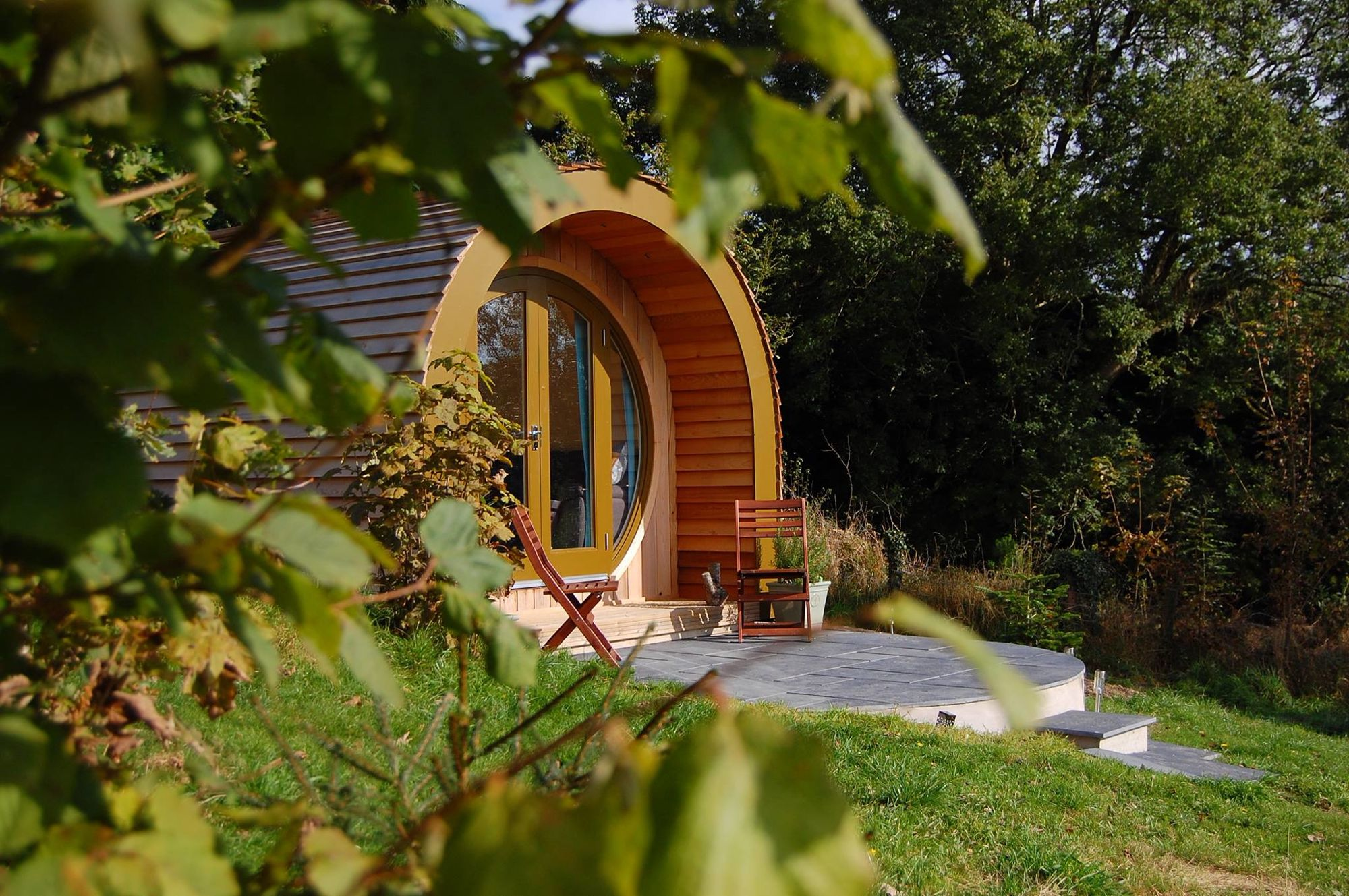 A single, cedar-clad luxury glamping pod in Ceredigion with stunning views over a Welsh valley and acres of private space.