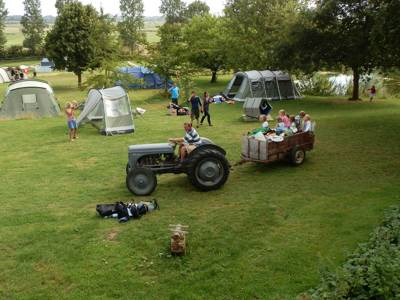 In the grounds of a thousand year old château commissioned by William the Conqueror, lies a brilliant family campsite with a limited number of pitches, a natural swimming pond and a vintage tractor that trundles you to and from your tent.