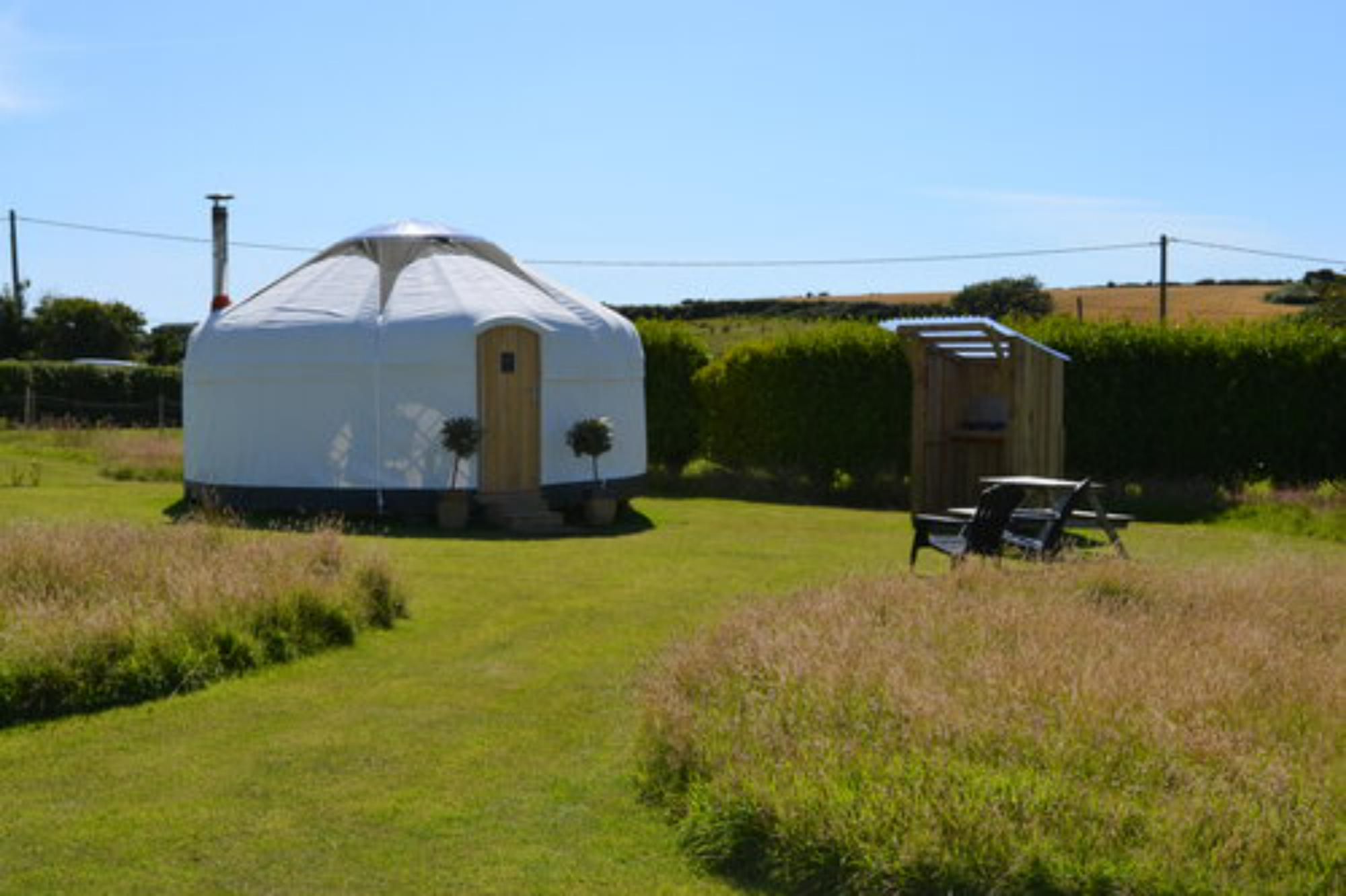 Outside, each yurt has a kitchen hut and a picnic table.