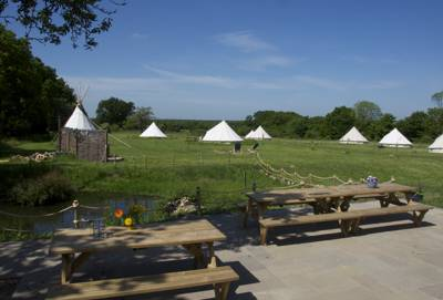 Luxury glamping accommodation in an old orchard cast against the pleasant greenery of rural Kent.