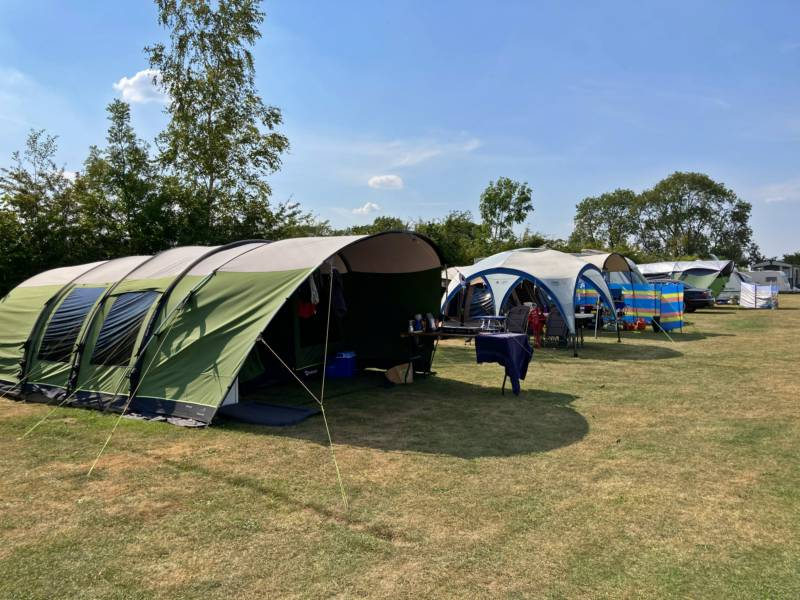 Family tents enjoy a sunny spot in the grassy camping meadow at Cotswold Hills Country Park.