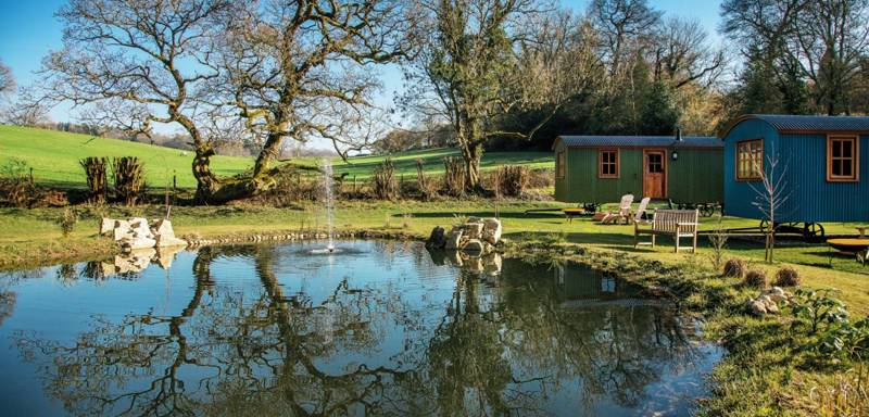 The shepherd's huts are set beside a small pond behind the country pub.