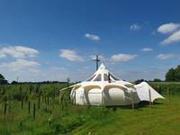 Lotus belle tent on a medieval moat in Norfolk